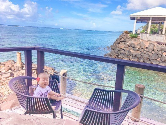 Happy Baby with flower sitting on chair at Saletoga Sands Resort Restaurant Bar with Turquoise Crystal Clear water